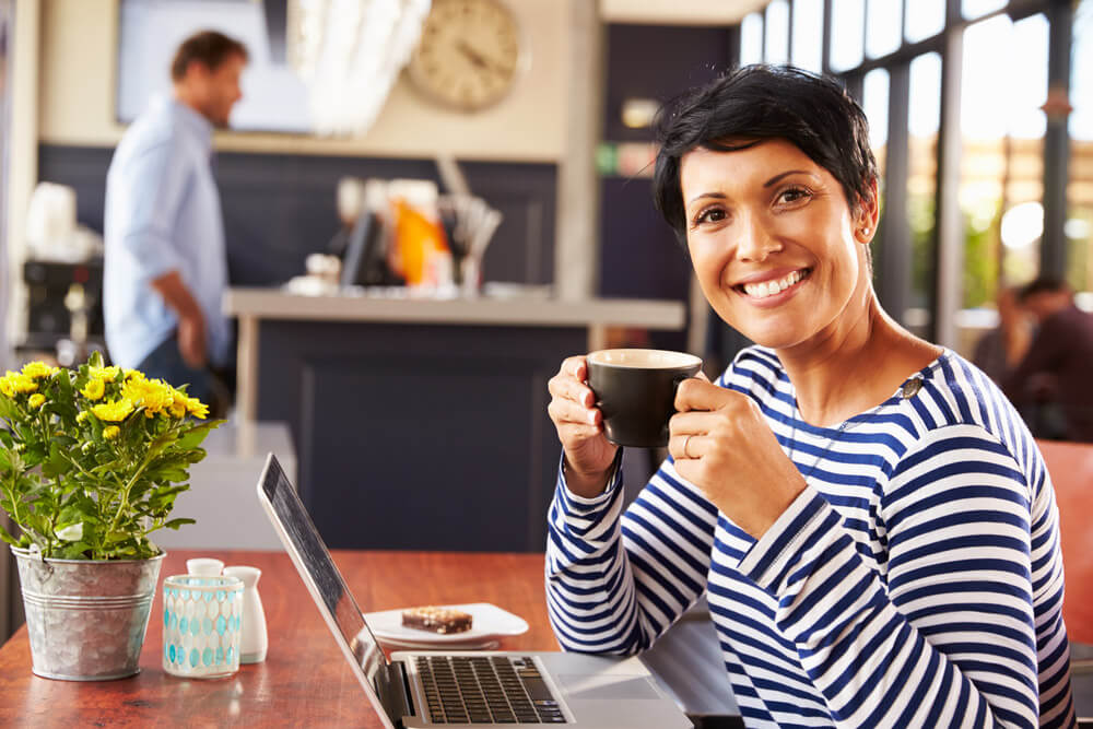 Woman smiling while having a cup of coffee in a coffee house