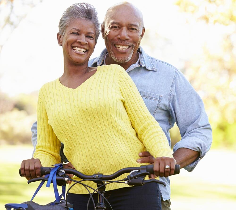 Older couple smiling while riding a bike
