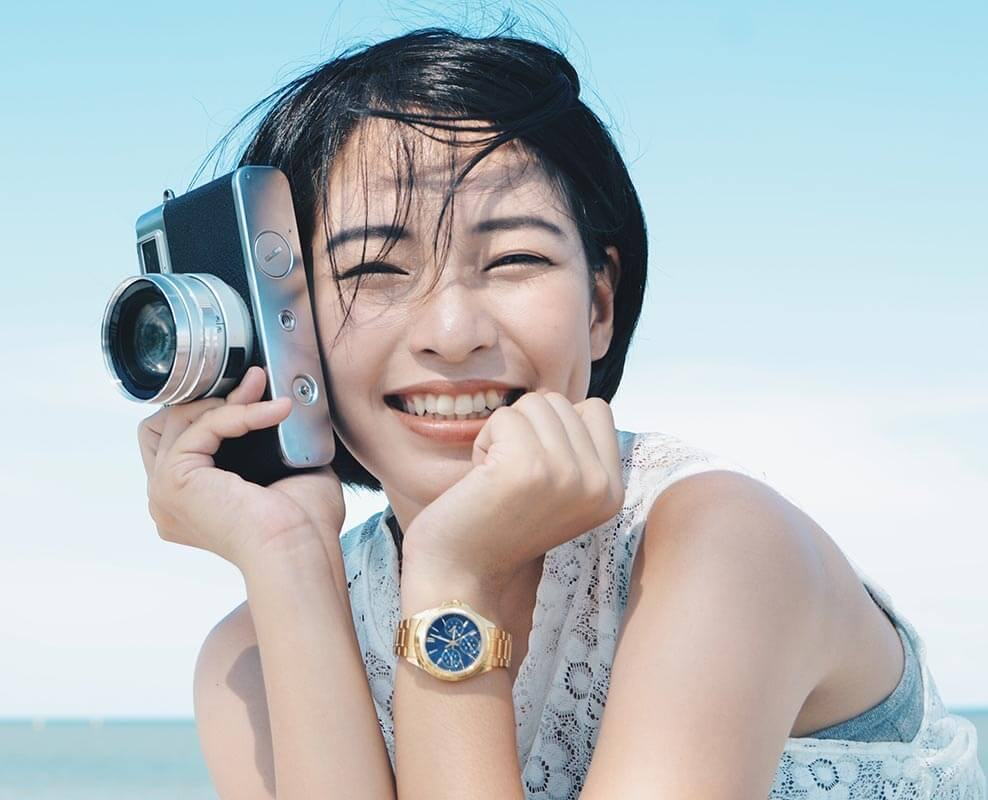 Young adult woman smiling and holding a camera