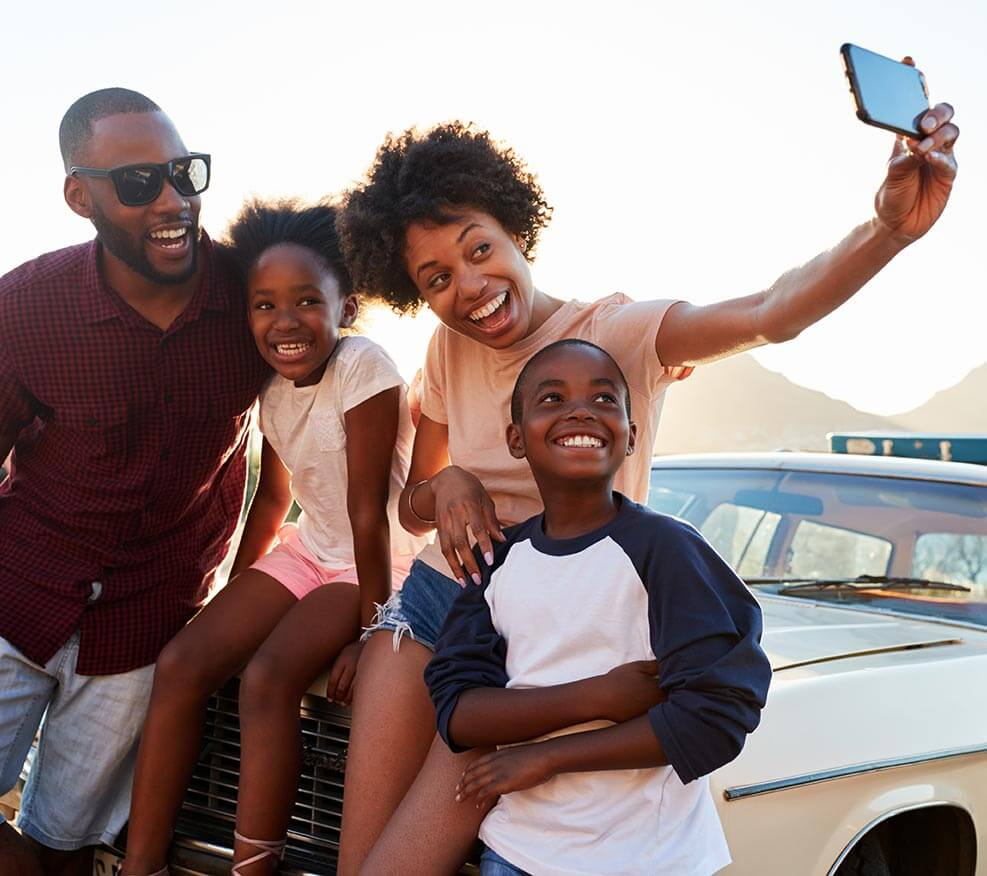 Young family taking a selfie with a car in the background