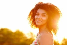 Smiling woman with warm, bright sun in the background