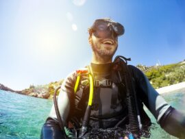 Smiling diver wearing goggles and scuba equipment waist deep in clear water near a shoreline