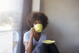 Woman sitting casually holding saucer plate and gazing over coffee while taking a sip from mug