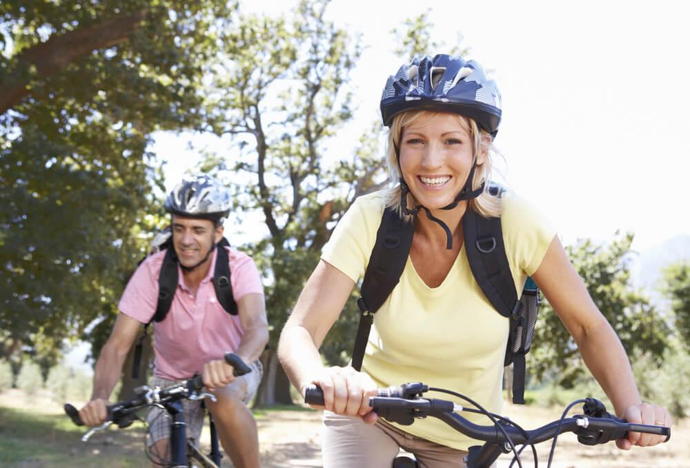 Man and woman outside riding mountain bikes