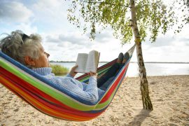 Older woman in hammock reading a book on the beach