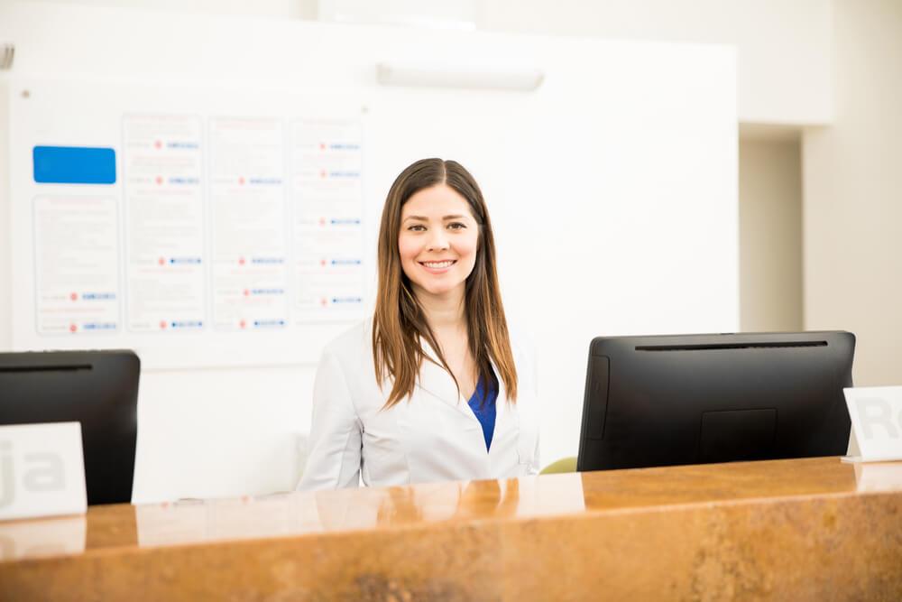 Smiling nurse at a reception desk