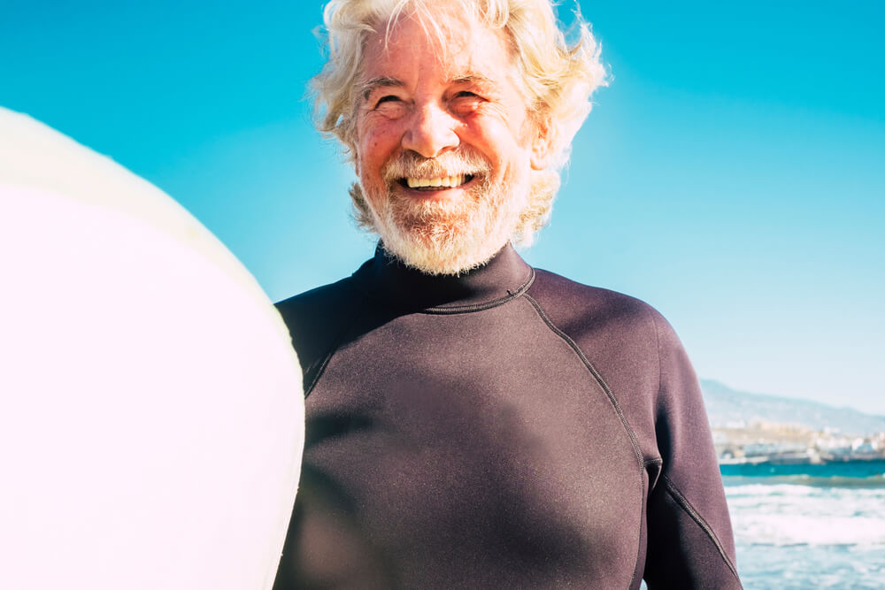 Smiling older man holding a surfboard at the beach