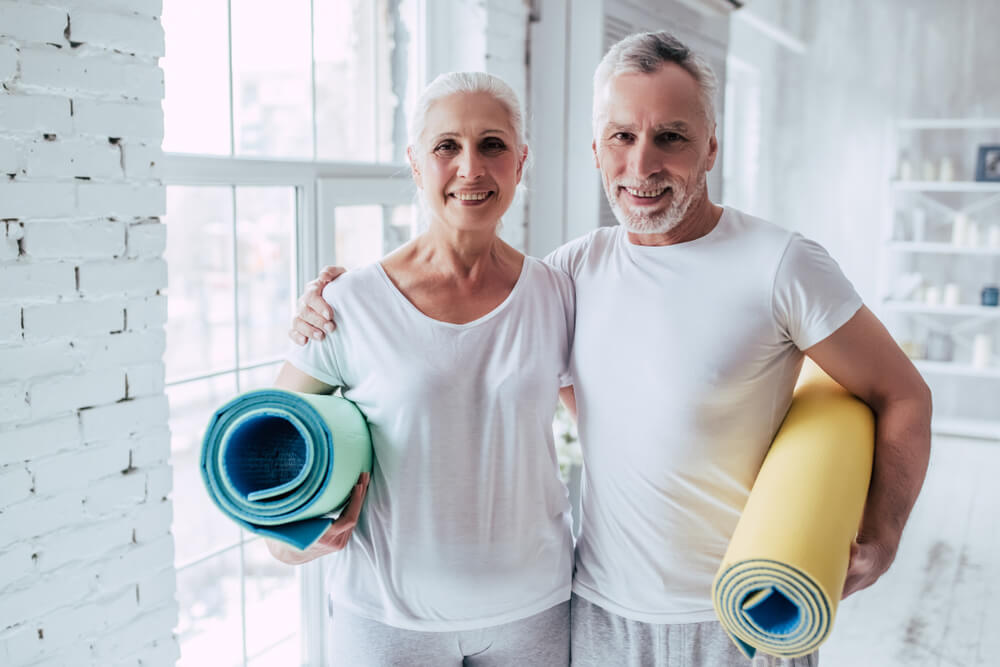 Happy older couple both holding rolled up yoga mats